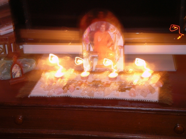 photo of altar after reading given by Comic Sai Baba. Photo shows three leelas with om symbol, Baba rising from photo and light circles around tea-lights